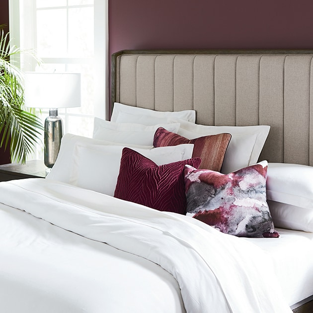 bed with decorative pillows and upholstered headboard